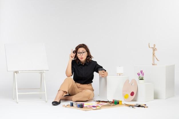 Вид спереди молодая женщина, сидящая внутри комнаты с красками и мольбертом на белом фоне