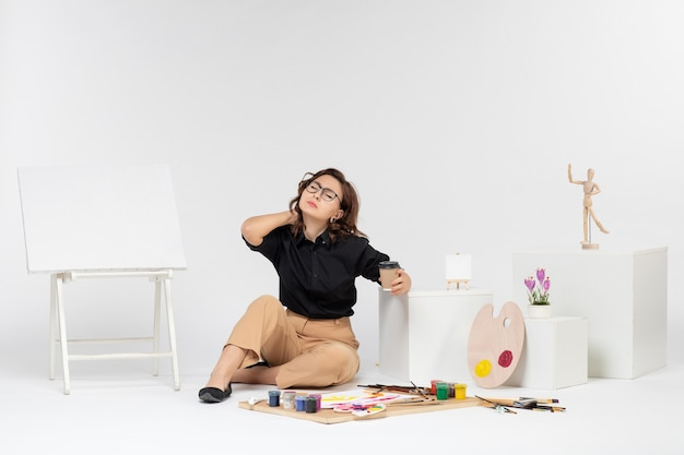 Front view young female sitting inside room with paints and easel having neckache on white background