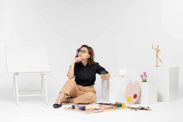 Front view young female sitting inside room with paints and easel on a white background