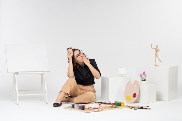 Front view young female sitting inside room with paints and easel on the white background