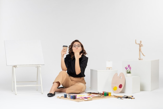 Front view young female sitting inside room with paints and easel on white background