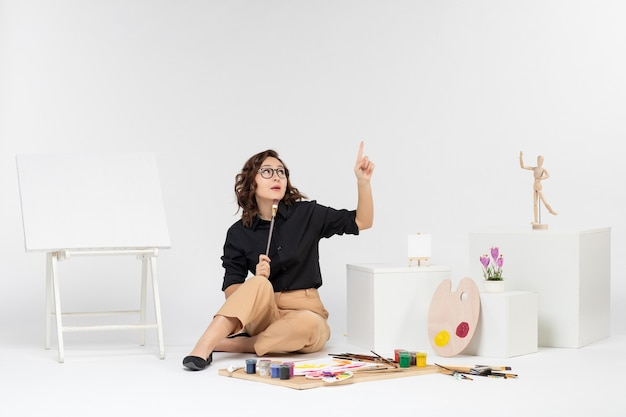 Vista frontale giovane donna seduta all'interno della stanza con pitture e cavalletto su sfondo bianco