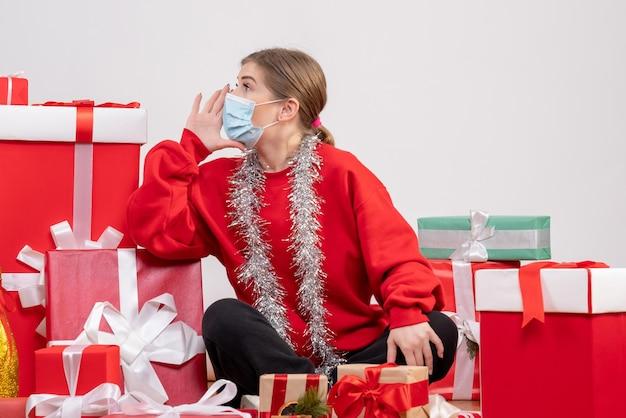 無菌マスクでクリスマスプレゼントと一緒に座っている正面図若い女性