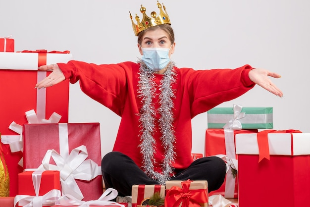 Front view young female sitting with christmas presents in mask and crown