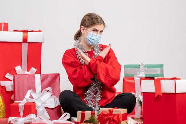 Giovane donna di vista frontale che si siede con i regali di natale nella mascherina sterile