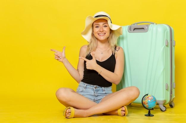 Giovane donna di vista frontale che si siede con la sua borsa e che si sente felice sul sole giallo di viaggio di viaggio di vacanza di viaggio della parete