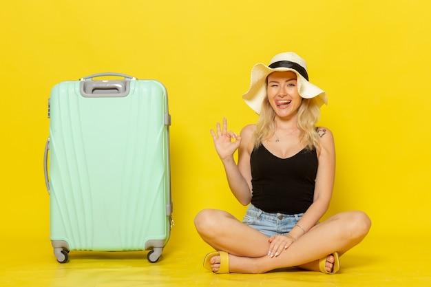明るい黄色の壁の旅の休暇の太陽の航海の旅の女の子に幸せを感じている彼女の緑のバッグと一緒に座っている正面図若い女性