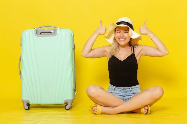 黄色の壁旅行休暇太陽航海旅の女の子に幸せを感じて彼女の緑のバッグと一緒に座っている正面図若い女性