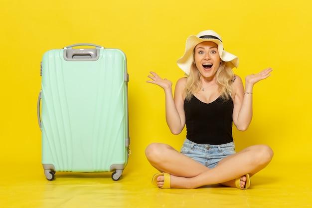 黄色の壁旅行休暇航海旅の女の子に幸せを感じて彼女の緑のバッグと一緒に座っている正面図若い女性