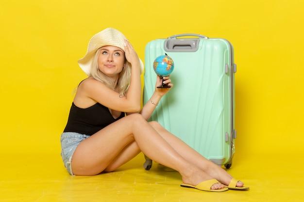노란색 벽 여성 여행 휴가 항해 바다 색 여행 태양에 지구본을 들고 그녀의 녹색 가방에 앉아 전면보기 젊은 여성
