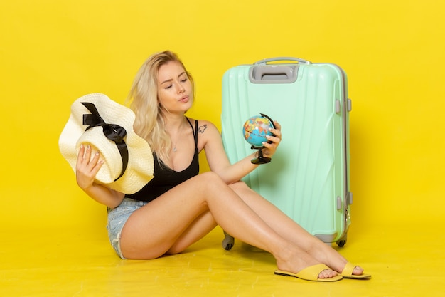 노란색 벽 여행 휴가 항해 바다 색 여행 태양에 지구본을 들고 그녀의 녹색 가방에 앉아 전면보기 젊은 여성