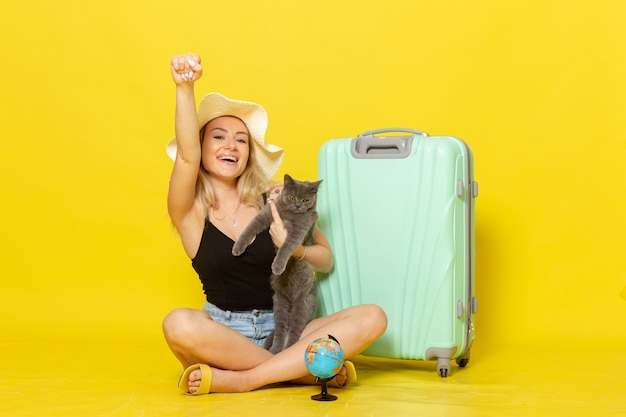 Front view young female sitting with her green bag holding kitten on light yellow wall trip vacation voyage sea color journey sun