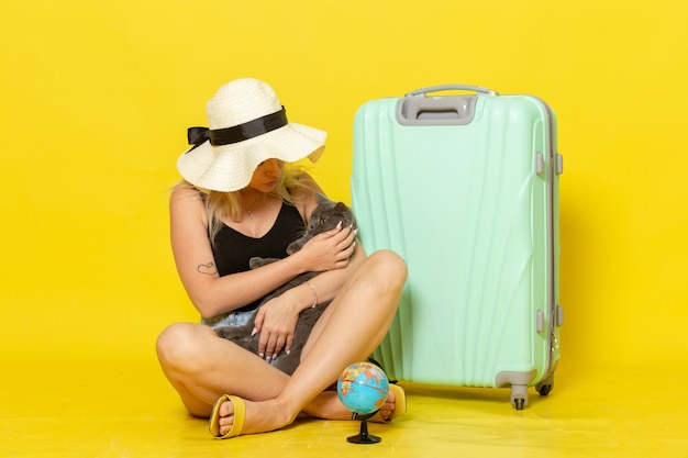 Front view young female sitting with her green bag holding kitten on yellow desk trip vacation voyage sea journey sun