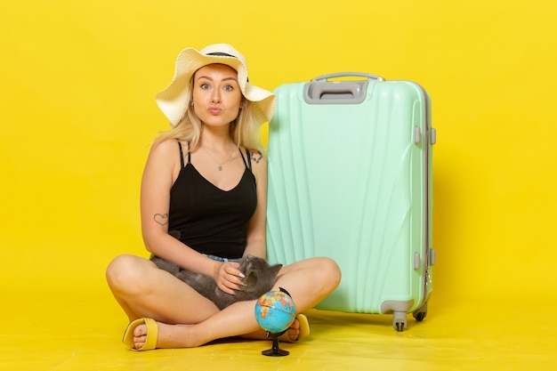 Front view young female sitting with her green bag holding kitten on yellow wall trip vacation voyage color journey sun
