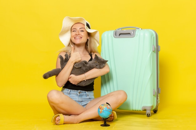 Front view young female sitting with her green bag holding kitten on a yellow wall trip vacation voyage sea color journey sun