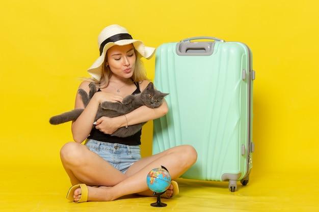 Giovane donna di vista frontale che si siede con il suo gattino verde della tenuta della borsa sulla parete gialla viaggio vacanza viaggio mare colore viaggio sole