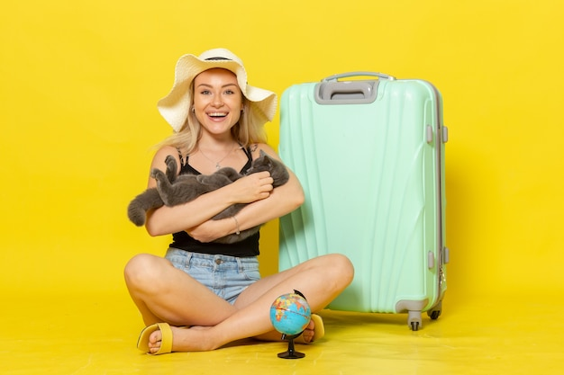 Front view young female sitting with her green bag holding kitten on yellow wall trip vacation voyage sea color journey sun
