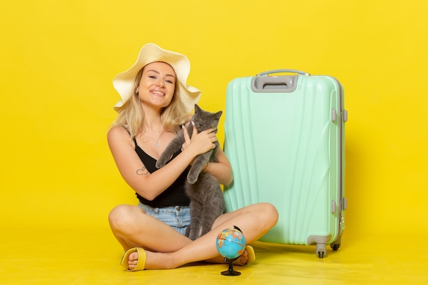 Front view young female sitting with her green bag holding kitten on a yellow wall trip vacation voyage sea journey sun