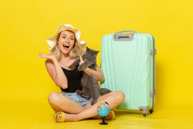 Front view young female sitting with her green bag holding kitten on the yellow wall trip vacation voyage sea journey sun