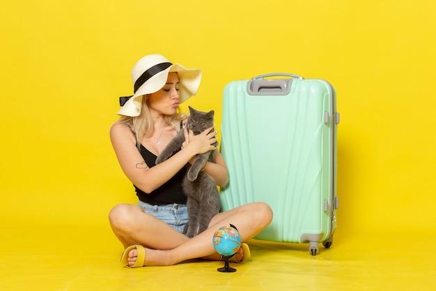 Giovane femmina di vista frontale che si siede con il suo gattino verde della tenuta della borsa sul sole giallo di viaggio di viaggio di vacanza di viaggio della parete