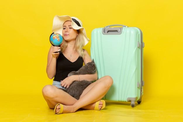 Вид спереди молодая женщина, сидящая со своей зеленой сумкой, обнимая котенка с глобусом на желтой стене, путешествие, путешествие, морское путешествие, солнце