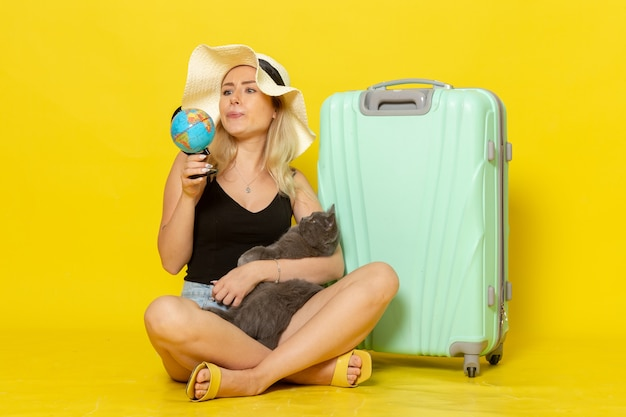 Front view young female sitting with her green bag hugging kitten holding globe on yellow wall trip vacation voyage sea journey sun