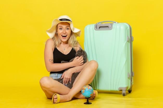 Вид спереди молодая женщина, сидящая со своей зеленой сумкой, обнимая котенка на желтой стене, путешествие, путешествие, морское путешествие, солнце