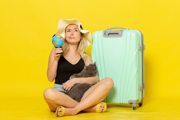 Front view young female sitting with her green bag hugging kitten on yellow desk trip vacation voyage sea journey sun