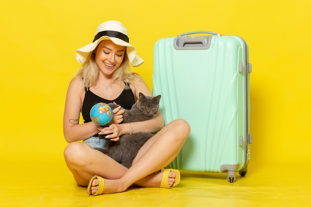 Front view young female sitting with her green bag hugging kitten on a yellow wall trip vacation voyage sea journey sun