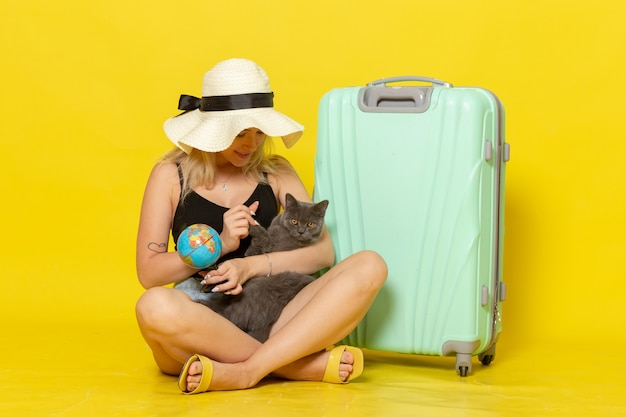 Front view young female sitting with her green bag hugging kitten on the yellow wall trip vacation voyage sea journey sun