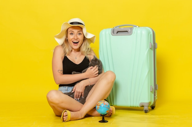 Front view young female sitting with her green bag hugging kitten on yellow wall trip vacation voyage sea journey sun