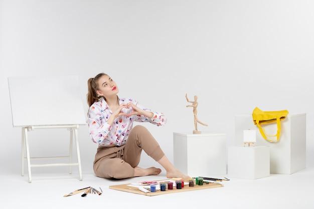 正面図白い背景で描くための塗料とイーゼルで座っている若い女性