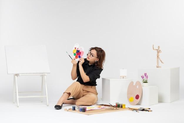 Вид спереди молодая женщина, сидящая с красками и мольбертом на белом фоне