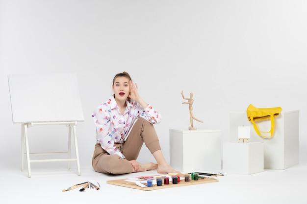 Vista frontale giovane donna seduta con cavalletto per vernici e pennelli su sfondo bianco