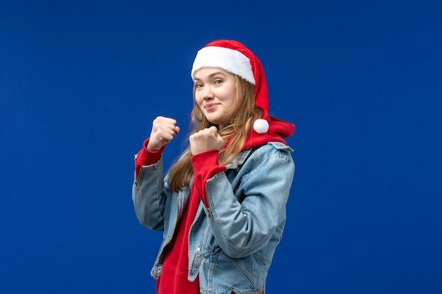 Вид спереди молодая женщина улыбается и показывает кулаки на синем фоне цвета рождественских эмоций