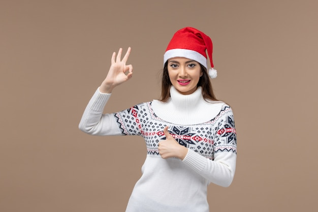 Vista frontale giovane donna sorridente con tappo rosso su sfondo marrone emozione natale capodanno