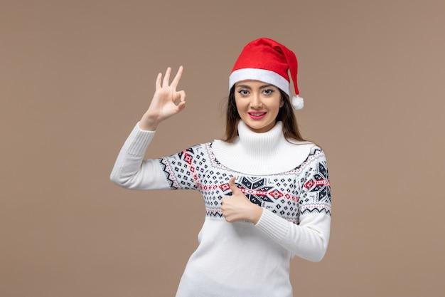 갈색 배경 감정 크리스마스 새 해에 빨간 모자와 함께 웃 고 전면보기 젊은 여성