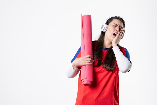 Front view young female in sport clothes holding yoga mat and having toothache