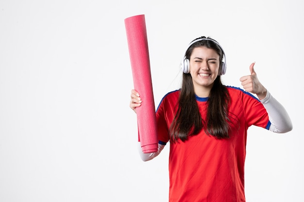 Front view young female in sport clothes holding yoga mat