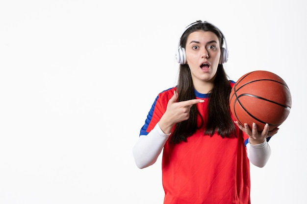 Front view young female in sport clothes with basketball on white wall