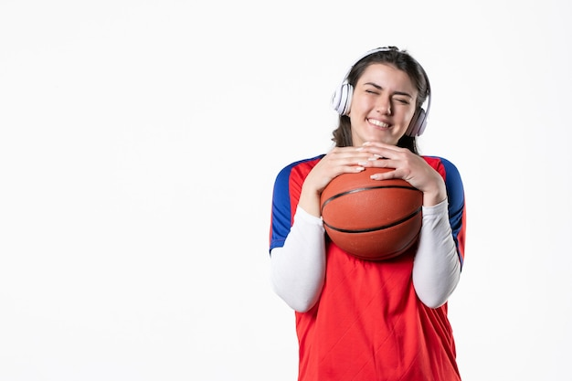 Front view young female in sport clothes with basketball