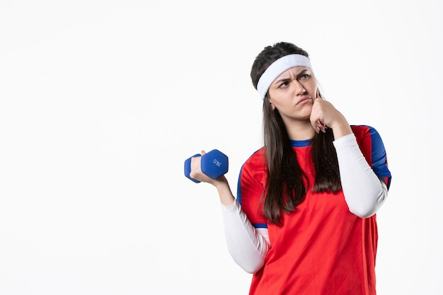 Giovane femmina di vista frontale in vestiti di sport con i dumbbells blu sulla parete bianca