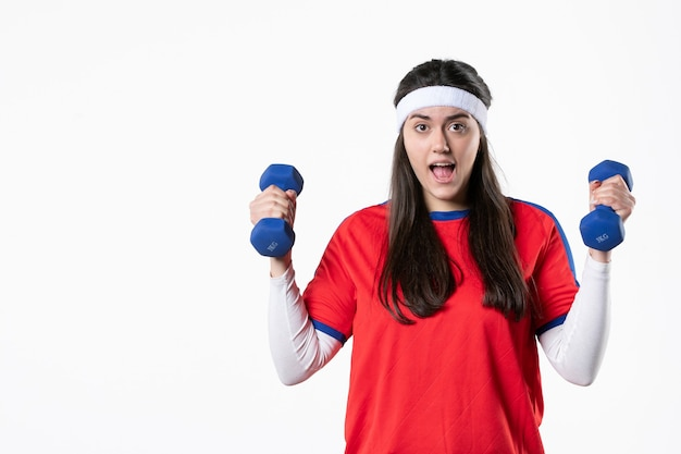 Front view young female in sport clothes with blue dumbbells on white wall