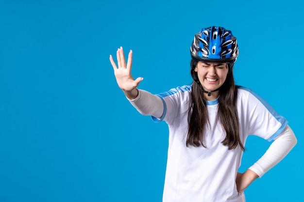 Giovane donna di vista frontale in abbigliamento sportivo con casco sulla parete blu