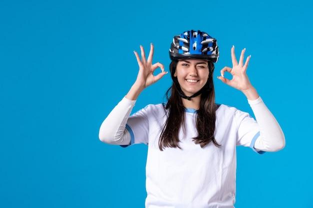 Giovane femmina di vista frontale in vestiti di sport con il casco sulla parete blu