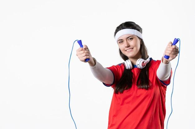 Giovane femmina di vista frontale in vestiti di sport con le corde di salto sulla parete bianca