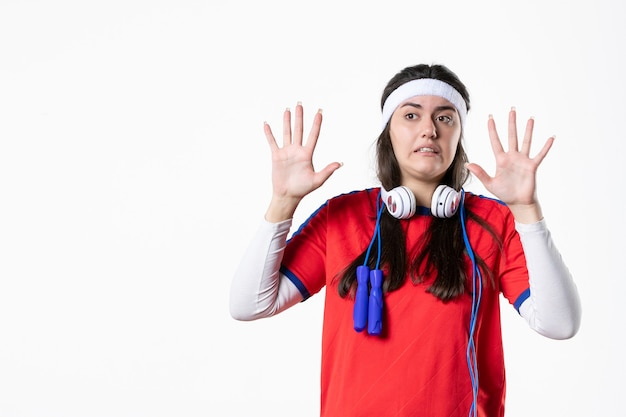 Front view young female in sport clothes with skipping ropes on white wall