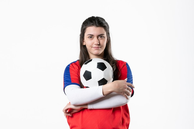Front view young female in sport clothes with soccer ball on white wall