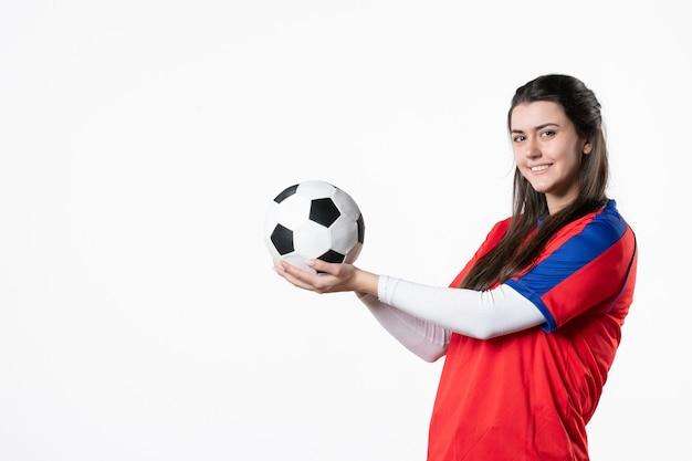Giovane femmina di vista frontale in vestiti di sport con il pallone da calcio sulla parete bianca
