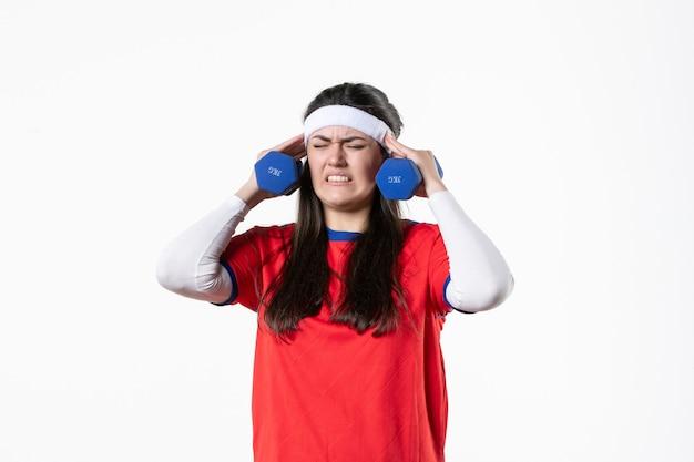 Giovane femmina di vista frontale in vestiti di sport che risolve con i dumbbells sulla parete bianca